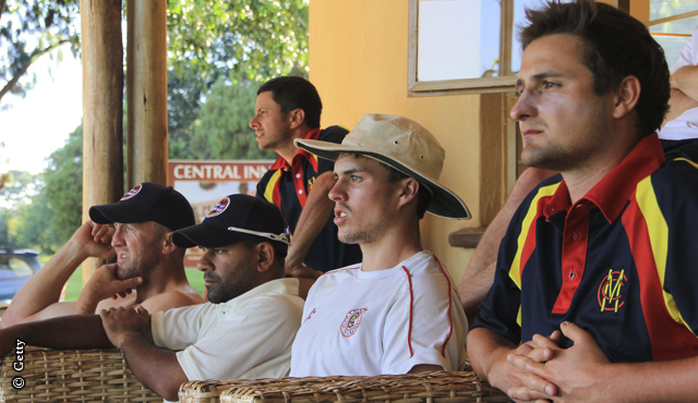 The players watch on from the pavilion