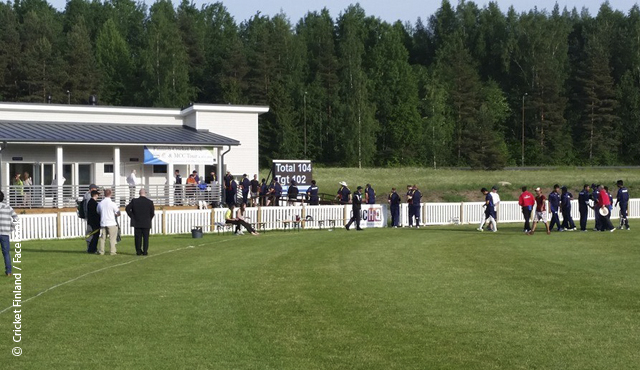 The teams leave the field at Kerava National Cricket Ground after Finland win the T20