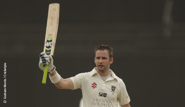Durham's Mark Stoneman raises his bat after making a century